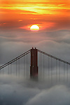 The morning sun peeks over a blanket of fog with the Golden gate Bridge in the foreground.