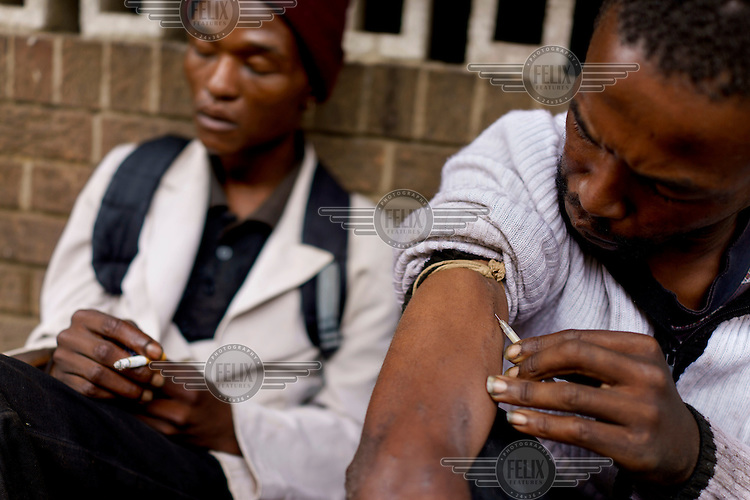 Sfiso, a drug user, injects himself with a used syringe of 'nyaope' on a street in Hillbrow, an inner-city neighbourhood with a reputation as a centre for illicit drug use. 'Nyaope' is usually described as a crude form of heroin cut with anything from anti-retrovirals to rat poison to pool cleaner. It is cheap,  at about 20 Rand or GBP 1.11, and addictive.