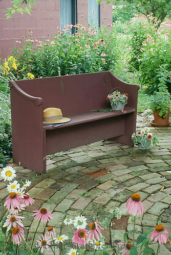 Lovely antique round brick patio in shaded side yard with bench for seating made from a church pew and splashes of color from blooming gardens and cut flowers
