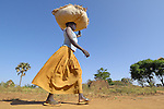 A woman carries a bag of grain in the Omiya camp for internally displaced families. Two decades of war in northern Uganda have left almost two million people displaced, though progress in peace talks in 2006 initiated a small movement to return to home villages.