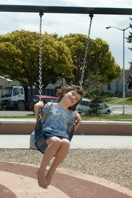 Berkeley CA Girl, four-years-old happily swinging herself at park  MR