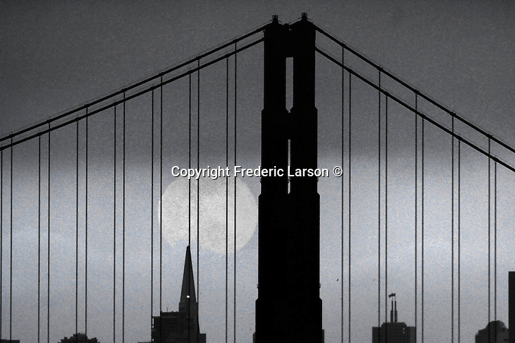 The full moon of May rose near the south tower of the Golden Gate Bridge and the TransAmerican Pyramid as seen from the Marin Headlands.