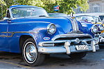 Havana, Cuba; a classic blue 1953 Pontiac convertible parked next to a yellow and a purple 1954 Chevys on the street in Old Havana
