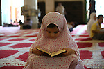 A Palestinian girl reads the Qur'an during the holy fasting month of Ramadan at al-Aqsa mosque, Islam's third holiest site, in Jerusalem's Old City on June 30, 2014. Muslim believers abstain from eating, drinking, smoking and having sex from dawn until sunset. Ramadan is sacred to Muslims because it is during that month that tradition says the Koran was revealed to the Prophet Mohammed. Photo by Saeed Qaq