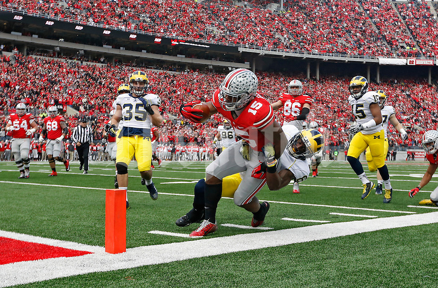 Ohio State Buckeyes running back Ezekiel Elliott (15) gets pulled down my Michigan Wolverines defensive back Raymon Taylor (6) at the 2 yard line in the 1st quarter of their game at Ohio Stadium in Columbus, Ohio on November 29, 2014.  (Dispatch photo by Kyle Robertson)