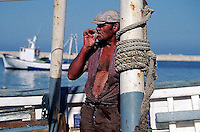 Alicante--- A fisherman takes a moment to smoke a cigarette. Spain. --- Image by &copy; Owen Franken/CORBIS
