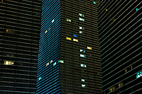 High rise blocks with individual apartments illuminated by their interior lighting.
