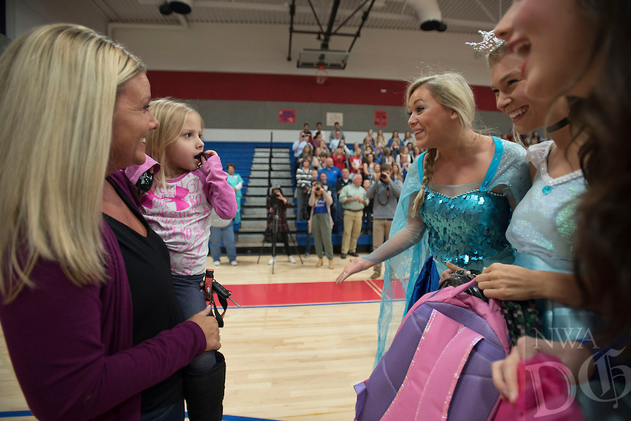 NWA Democrat-Gazette/J.T. WAMPLER  Harper Gillespie, 5, held by her mother Kyla Gillespie of Springdale, is greeted Monday Nov. 9, 2015 by a trio of Disney princesses played by University of Arkansas Chi Omega sorority members Madeline Wagnon, (from the right) Catherine Cain and Elise Jones. The princess and the rest of the Chi Omega sorority was on hand at George Middle School to tell Harper her wish to go to Disney World has been granted by Make-A-Wish Mid-South. Harper was born with a collapsed trachea and has had several surgeries.
