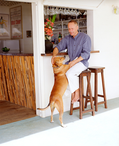 CASTLE BRUCE, DOMINICA : Beau Rive owner and British ex-pat Mark Steele plays with Winston the dog outside the roof top terrace bar at Beau Rive Hotel in Dominica. Beau Rive is situated 240 feet above sea level on the East (Atlantic) coast between the villages of Castle Bruce and Sineku. The hotel is nestled into a hillside amid three acres of tropical gardens and forest, with a dramatic view of the ever-crashing waves at Anse Francais and Wakaman Point. Dominica.