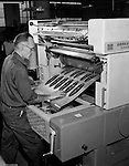 Pittsburgh PA - View of a printing press operator creating a printing plate using the Harris printing equipment.  On site photography at Colonial Press Company at the Try Street Terminal Building.<br /> Colonial Press merged with Herbick and Held Printers in 1958 and operated as a division. During the 1980's hard times hit the city and business printers; Herbick and Held closed in 1984.