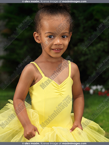 Portrait of a cute smiling three year old black girl wearing a yellow tutu dress