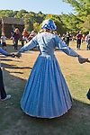 Old Bethpage, New York, U.S. 29th September 2013. Seen from behind, an Old Bethpage Dancer dressed in a blue Civil War era dress is dancing with visitors at The Long Island Fair. A yearly event since 1842, the county fair now is held at a reconstructed fairground at Old Bethpage Village Restoration.
