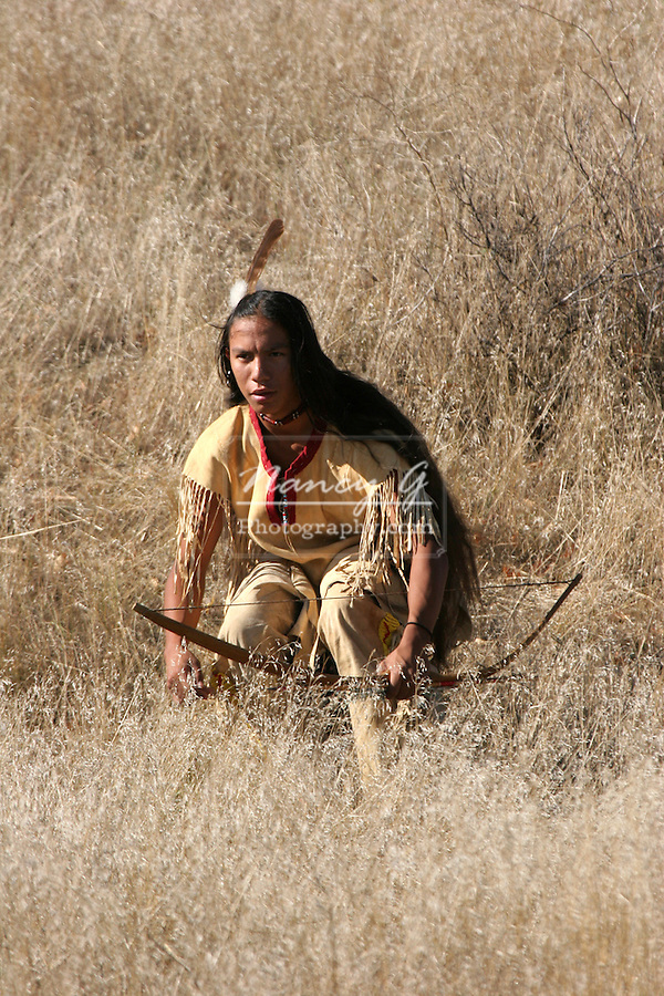 A Native American Indian boy crouching in the dead grasses hunting game with a bow and arrow