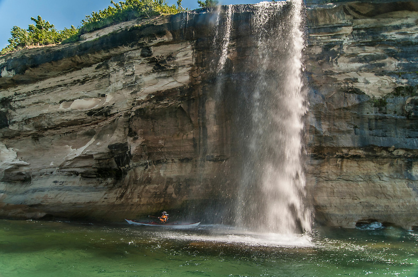 Kayakers paddle near Spray Falls on Lake Superior at Pictured Rocks National Lakeshore near Munising, Michigan.