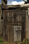 Wooden shed door with rusted hinges and horseshoes nailed to door. North Yorkshire, England.