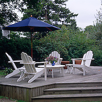 A group of white garden chairs and a blue parasol on a raised teak deck in the garden