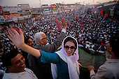 Rawalpindi, Pakistan<br /> November 10, 1988<br /> <br /> Benazir Bhutto arrives at a campaigns rally in Rawalpindi.<br /> <br /> Benazir Bhutto is the eldest child of former Pakistan President and Prime Minister Zulfikar Ali Bhutto. She found herself placed under house arrest in the wake of her father's imprisonment and subsequent execution in 1979. In 1984 she became the leader in exile of the Pakistan Peoples Party (PPP), her father's party, though she was unable to make her political presence felt in Pakistan until after the death of General Muhammad Zia-ul-Haq. <br /> <br /> On 16 November 1988 Benazir's PPP won the largest bloc of seats in the National Assembly. Bhutto was sworn in as Prime Minister in December, at age 35 she became the first woman to head the government of a Muslim-majority state in modern times. <br /> <br /> She was removed from office 20 months later under orders of then-president Ghulam Ishaq Khan for alleged corruption. Bhutto was re-elected in 1993 but was again removed by President Farooq Leghari in 1996, on similar charges. Bhutto went into self-imposed exile in Dubai in 1998, until she returned to Pakistan on October 2007, after General Musharraf granted her amnesty and all corruption charges withdrawn.