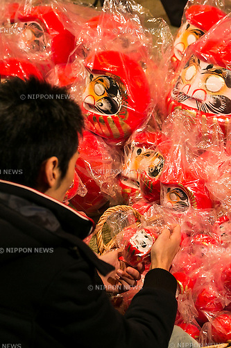 A man looks at the Daruma dolls on sale outside the Shorinzan Daruma Temple in Takasaki City, Gunma Prefecture on January 6, 2016, Japan. Every year thousands of people visit the country's most famous Daruma market (Daruma ichi) held at the Shorinzan Daruma Temple on January 6 and 7. Takasaki City, is known as the capital of Daruma dolls and about 80% of Japan's Daruma are produced there. According to the tradition, Daruma dolls are sold without pupils painted on their eyes. People color in one pupil when a wish is made or a goal set, and when the wish comes true or the goal is achieved they fill in the other pupil. At the end of the year, used Daruma dolls are returned to the temple to be burned. (Photo by Rodrigo Reyes Marin/AFLO)