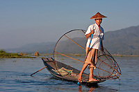Myanmar, Burma.  Fisherman Looking for a Place to Set his Fishnet while holding his paddle with one leg, in the style common to Inle Lake, Shan State.