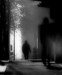 A silhouette of a man walking down a street
