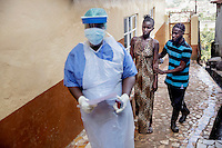 Isata Mansaray, 28, who is severely ill with ebola-like symptoms, is led, after a long wait, to a treatment facility in the Blackhall Road district. She died shortly afterwards and her family, who were unprotected, although contracted the virus.