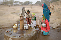 Early morning at a hand pump, Azmer district. Rajasthan has been suffering a drought for the last eight years and underground water levels are severely depleted. Water at hand pumps such as this one is starting to run out, forcing villagers to sometimes wait hours to get water for their daily needs...