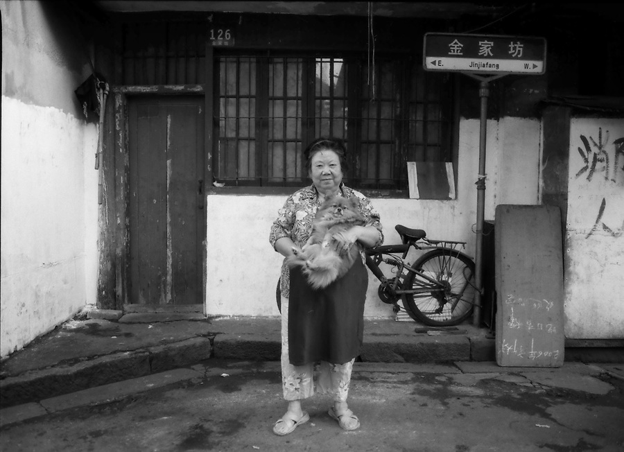 ..A woman holds a small dog in ront of her modest home in an old Shanghai neighborhood.