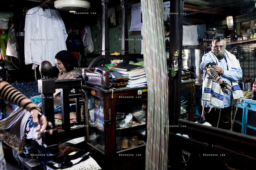 Orthodox Indian jew Solomon Ruben Galsurker (aged 61) puts tefillin in his one room home while his wife, Seema Solomon Galsurker (aged 58) folds their clothes. The couple have 4 sons and 1 daughter in Israel, with their youngest son, 22 year old Abner Solomon Galsurker still in India, studying commerce. They remain in India to take care of the Sha'ar Hattefilla synagogue in Mashla village where their family originate.