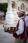 A man sells jasmine flowers in front of the Theatre Municipal in Tunis, Tunisia.  The tradition is for men to wear the flower behind their ear - the right ear if married and the left ear if single.