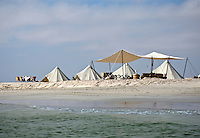 Tents in this luxury beach camp on the water's edge cluster around a covered relaxation area where a table is laid for lunch