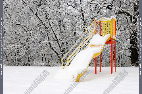 Colorful slide on a playground covered with snow wintertime scenic. High Park, Toronto, Ontario, Canada.