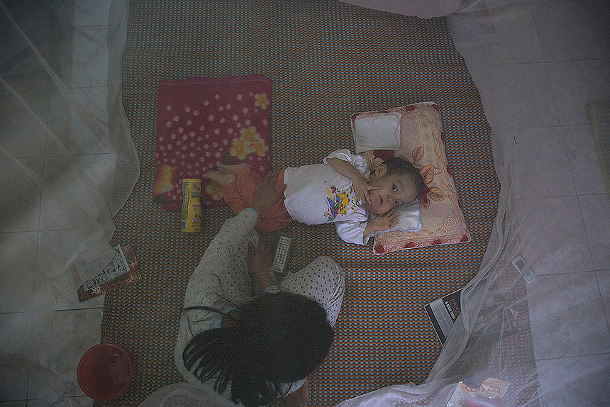 Nguyen Van Tuan Tu, a 7 year old boy suffering from serious health problems, is taken care of by a family member under mosquito net in their house near the airport in Danang, in central Vietnam April 12, 2015. When he started working at the Danang International Airport in 1997 Nguyen Van Tuan Tu's father was not aware of the danger - he was collecting snails and fish from a lake near the airport which has been contaminated by the defoliant Agent Orange and bringing them home to eat. His first child after started working at the airport, a daughter was born in 2000 and died in 2007. Nguyen Van Tuan Tu was born in 2008 with same symptoms as his late sister and doctors and parents believe their health problems are linked to effects of the Agent Orange. The couple has one healthy daughter that was born in 1995 before they started working at the airport and it's now an university student. Danang airport was a former a U.S. airbase during the war and since 2012 both U.S. and Vietnam are cleaning up the toxic chemical defoliant Agent Orange from parts of it.  REUTERS/Damir Sagolj