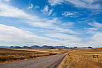 A gravel road stretches across the Central Montana plains before vanishing in the distant hills on a warm spring day.