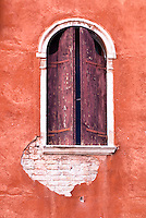 Venetian window and shutters against an orange wall, Venice, Italy