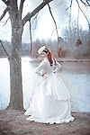 A regal young woman in a fancy wedding dress by a pond