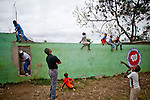Kids and onlookers watch a ball fly over the outfield wall during a showcase for Major League Baseball scouts on Friday, February 26, 2010 in San Antonio de Guerra, Dominican Republic.