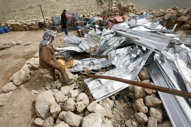 Palestinians sits next to her belongings following the demolition of her home aftar Israeli army bulldozer destroys a Palestinian home, in the village of Khirbet Tana near the West Bank city of Nablus, in the so-called Area C, a closed military zone where Israel exercises full control. ,Feb. 20, 2011 . Photo by Wagdi Eshtayah