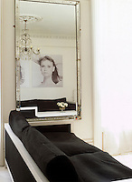 Black and white portraits are reflected in a large mirror in this contemporary living room