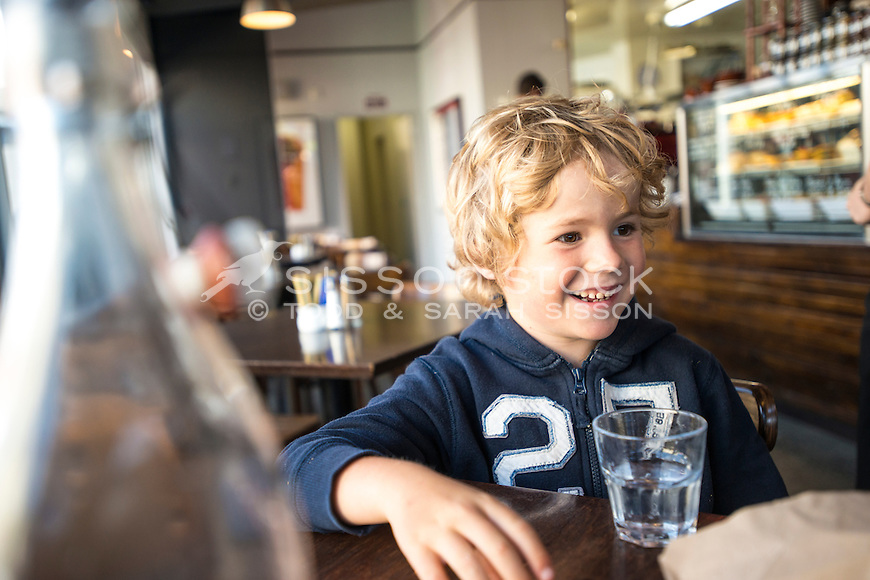 Young boy sitting at a table in a cafe, smiling across table, wait staff in the background, Dunedin, New Zealand - stock photo, canvas, fine art print