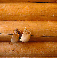 A pair of wooden teacups hang from pegs in the log cabin wall