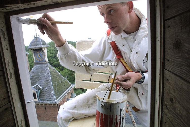 Foto: VidiPhoto..DOORWERTH - Via een zelfgefabriceerde constructie van balken met de rugsteun van een tuinstoel, en vastgemaakt met veiligheidsriemen, balanceert een werknemer van het gespecialiseerde schildersbedrijf Oostveen op het schuine leidak van kasteel Doorwerth. De schilders van het bedrijf moeten ruim twintig dakkapellen van het Rijnkasteel van een nieuwe verflaag voorzien. De werkzaamheden duren nog zeker drie weken.