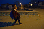 Yarely Arellano walks home at night through a darkened neighborhood in the Mexican city of Juarez after crossing the border from the United States, where she studies at the Lydia Paterson Institute, a United Methodist sponsored high school in El Paso, Texas. Arrelano, 20, makes the journey every school day.
