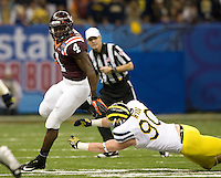 David Wilson of Virginia Tech runs the ball away from Michigan defender during Sugar Bowl game at Mercedes-Benz SuperDome in New Orleans, Louisiana on January 3rd, 2012.  Michigan defeated Virginia Tech, 23-20 in first overtime.
