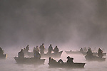 Opening day of fishing on Martha Lake at sunrise in fog with silhouetted fishermen in small boats fishing, Snohomish County Washington State USA..