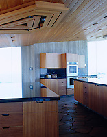 The functional open-plan kitchen benefits from spectacular views of the exterior through the glass walls