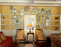 A collection of photographs is displayed in frames of differing shapes and sizes above two cane-backed chairs in the hotel bar
