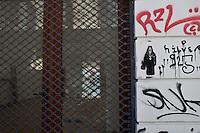 Atene, negozi chiusi in pieno centro in seguito alla crisi economica, serranda chiusa, scritte sul muro e icona di prete ortodosso