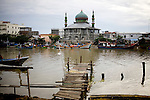 Fishing Boats return from sea along the Aceh River, in Banda Aceh, Indonesia, Thursday, Nov. 19, 2009. Locals pick the remaining fish from nets.