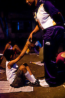Razia Shabnam (in dark blue) assists a child with sit-ups while she conducts a training session in Biyam Samiti park with children from the area of Kidderpore, Calcutta, West Bengal, India. Razia Shabnam, 28, was one of the first women boxers in Kolkata. She was also the first woman in her community to go to college. She is now a coach and one of only three international female boxing referees in India.  Photo by Suzanne Lee for Panos London