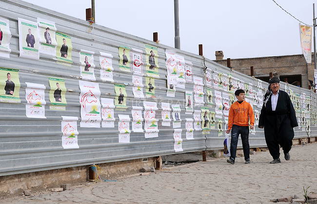SULAIMANIYAH, IRAQ:  A man a boy walk past a corrugated iron wall covered in election posters on the first day of official election campaigning...Election workers start their campaigns for the Iraqi Parliamentary Elections due to be held March 7th, 2010...Photo by Pazhar Muhammed/Metrography